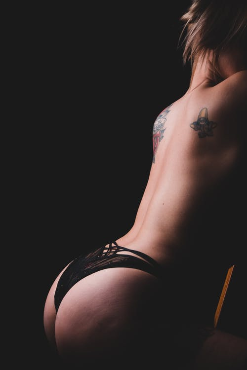 Side view of faceless slim sensual topless woman in underpants with tattoos on back on black background