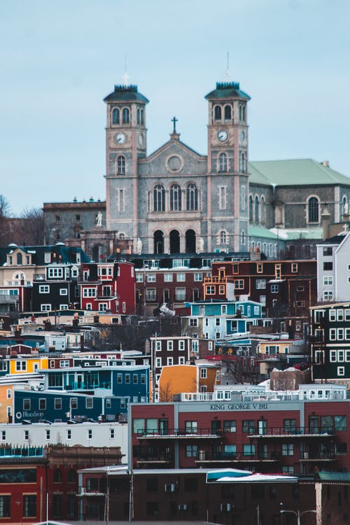 Basilica Cathedral of Saint John the Baptist by small multi colored houses on mountain slope in Newfoundland and Labrador in Canada