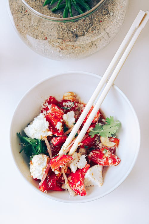 Delicious salad with tomatoes and tofu cheese in ceramic bowl