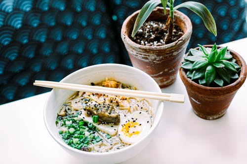 Top view of yummy Asian soup with chicken broth and noodles decorated with green onions and boiled egg in ceramic bowl with wooden chopsticks near plants in pots