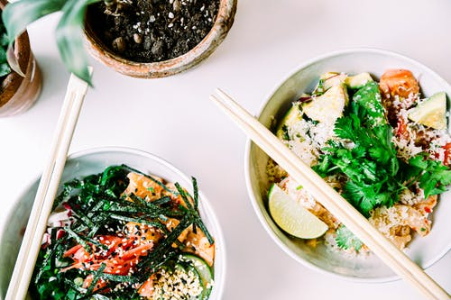 Top view of Asian salads with fish and shrimps decorated with fresh parsley and seaweeds in ceramic bowls with chopsticks on while table