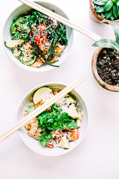Top view of deep ceramic bowls with chopsticks and vegetable salads with slices of lime and parsley near potted plants on white table