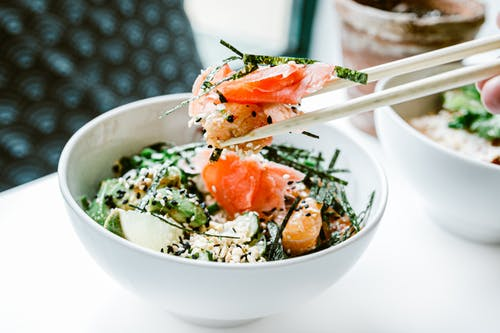 From above of crop faceless person with wooden chopsticks demonstrating Asian salad with salted salmon and seaweeds decorated with sesame seeds in ceramic bowl