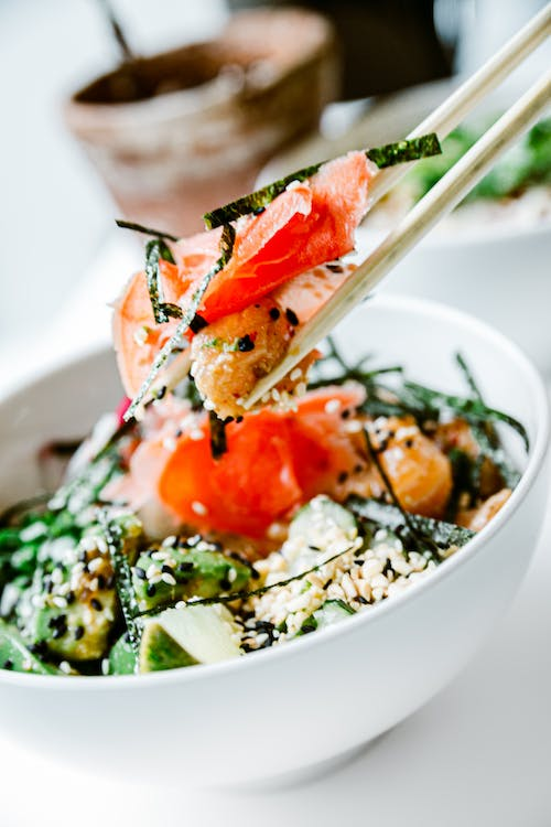 Asian salad with salmon and seaweeds in bowl in restaurant