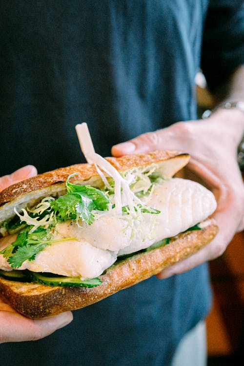 Crop anonymous man with delicious Asian fish sandwich