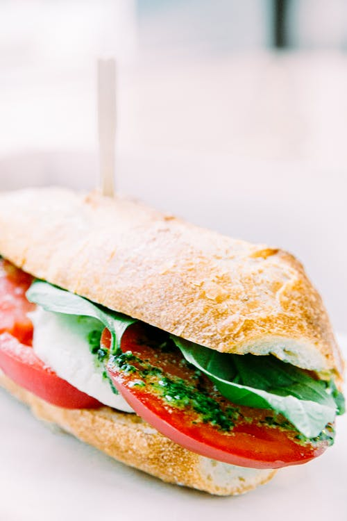 Delicious sandwich with ripe tomatoes and fresh basil leaves