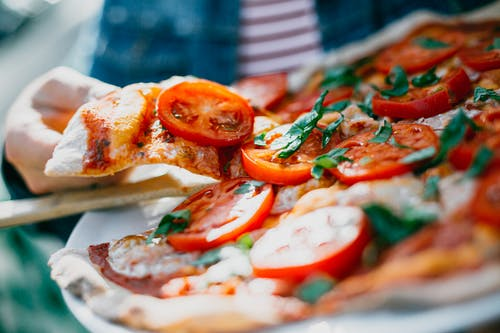 Closeup of crop unrecognizable person showing thin slice of yummy pizza decorated with ripe tomatoes and fresh basil on plate