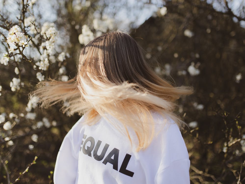 Faceless female in white oversize sweater with straight blonde flying hair in sunlight next to blooming tree in park