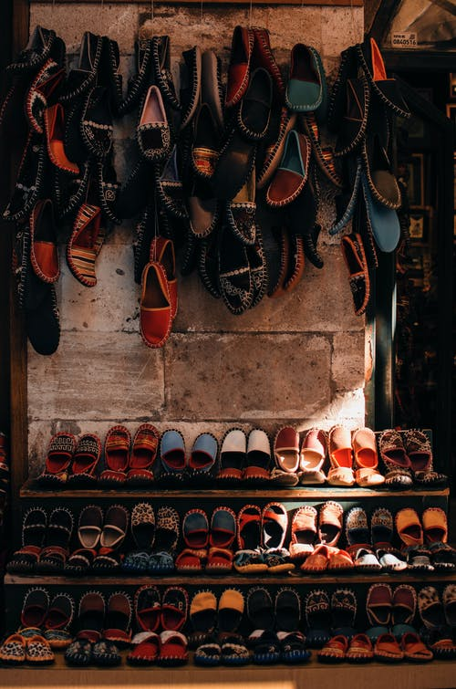 Colorful traditional shoes hanging on wall and placed on shelves