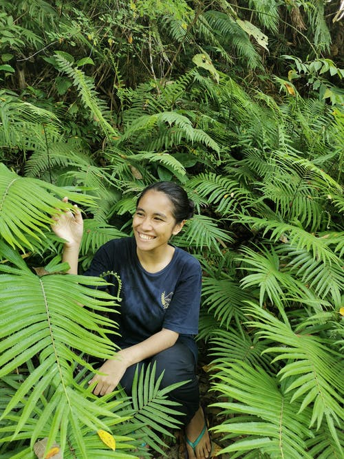 Cheerful Asian woman in green plants