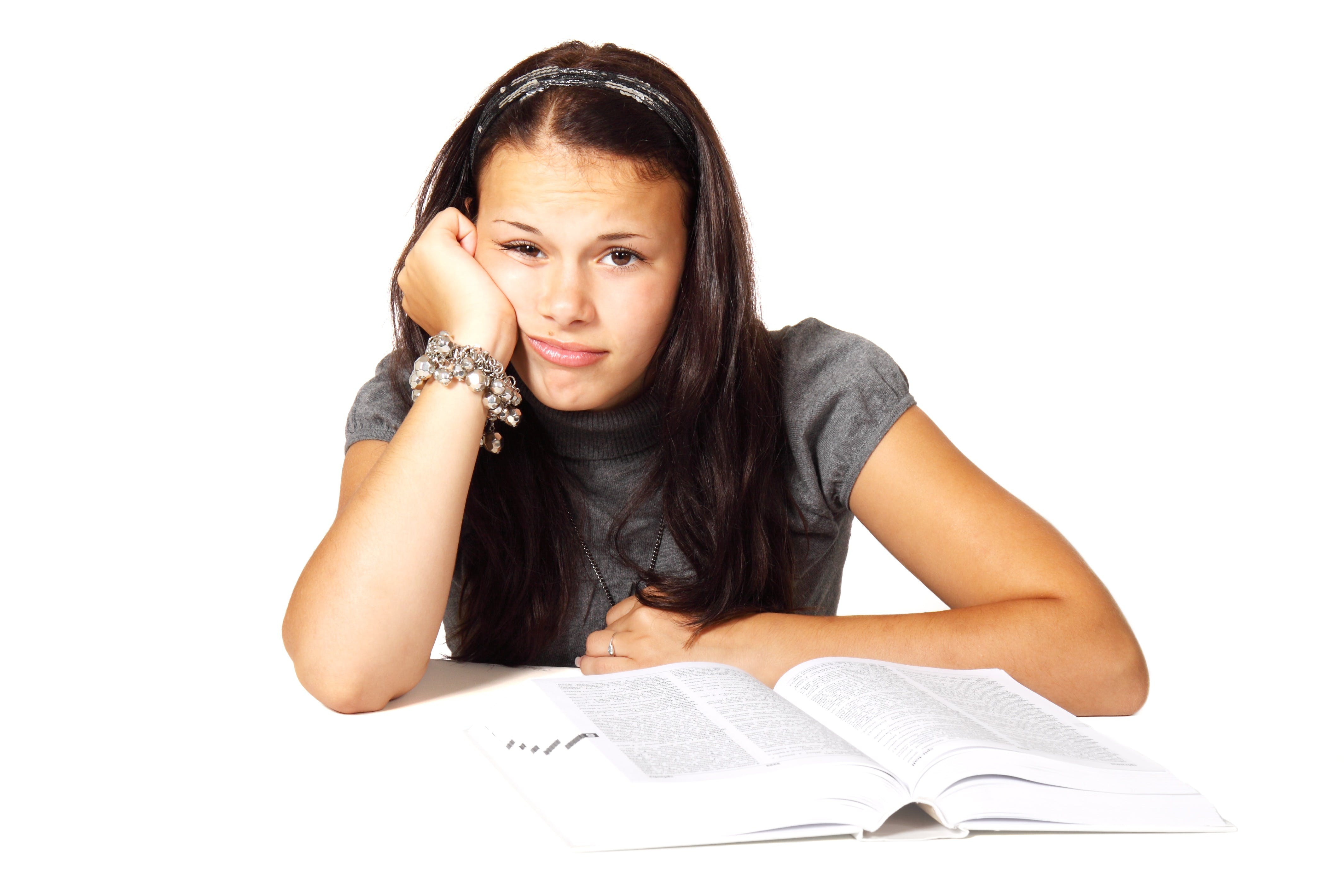 Woman in Black T-shirt Leaning on White Table in Front of White Book