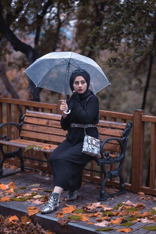 Woman with umbrella resting on bench