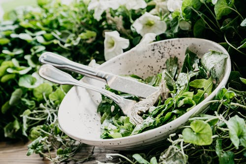 Green vegetable on white ceramic bowl with cutlery