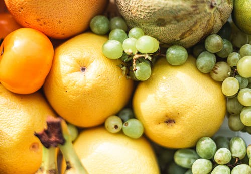 Top view of various ripe yellow and orange color fruits and green grape arranged on stall on street market in bright sunny day