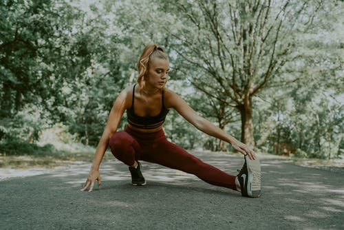 Flexible sportswoman doing lunges forward exercise