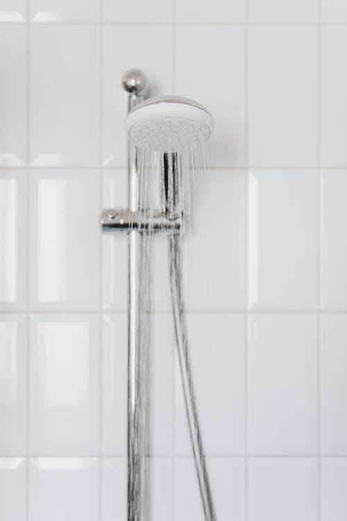 Stainless Steel Shower Head on White Ceramic Tiles