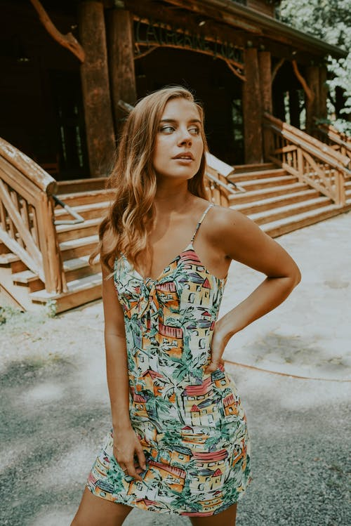 Charming young female wearing summer dress standing with hand on waist and looking away