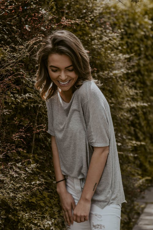 Young smiling woman standing near tree branches
