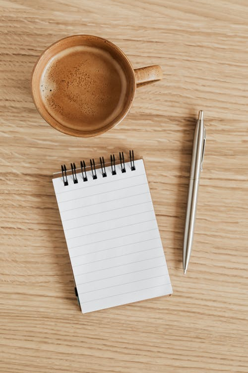 Top view of beige ceramic cup of aromatic espresso placed near ring bound notebook with blank sheet and silver pen on wooden tabletop