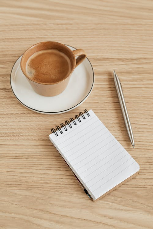 From above of opened notebook with blank sheet near silver pen composed with fragrant cup of hot espresso placed on wooden table