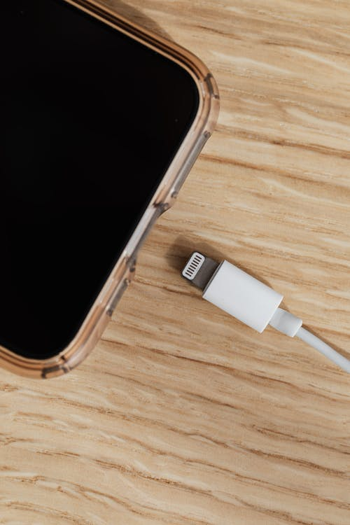 Smartphone and charger usb connector on wooden table