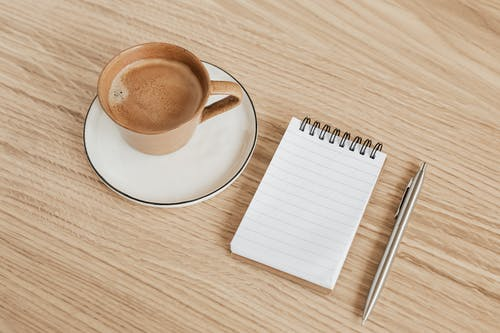 From above of ceramic cup of hot espresso on white saucer placed near opened ring bound notebook and stylish silver pen on wooden surface