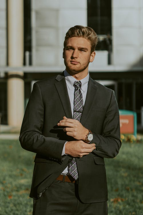 Successful businessman in elegant suit standing on street