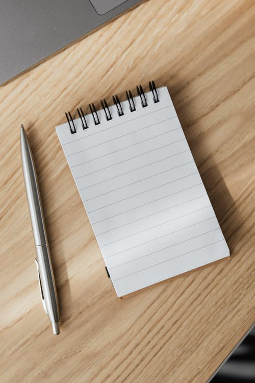 From above of small opened notepad and stylish silver pen placed on wooden table near laptop