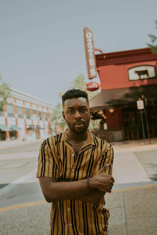 Kostnadsfri bild av afroamerikansk man, armarna korsade, armband, byggnad