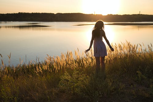 Back view of unrecognizable female in sundress enjoying river while standing on grass under shiny sky at sundown in back lit