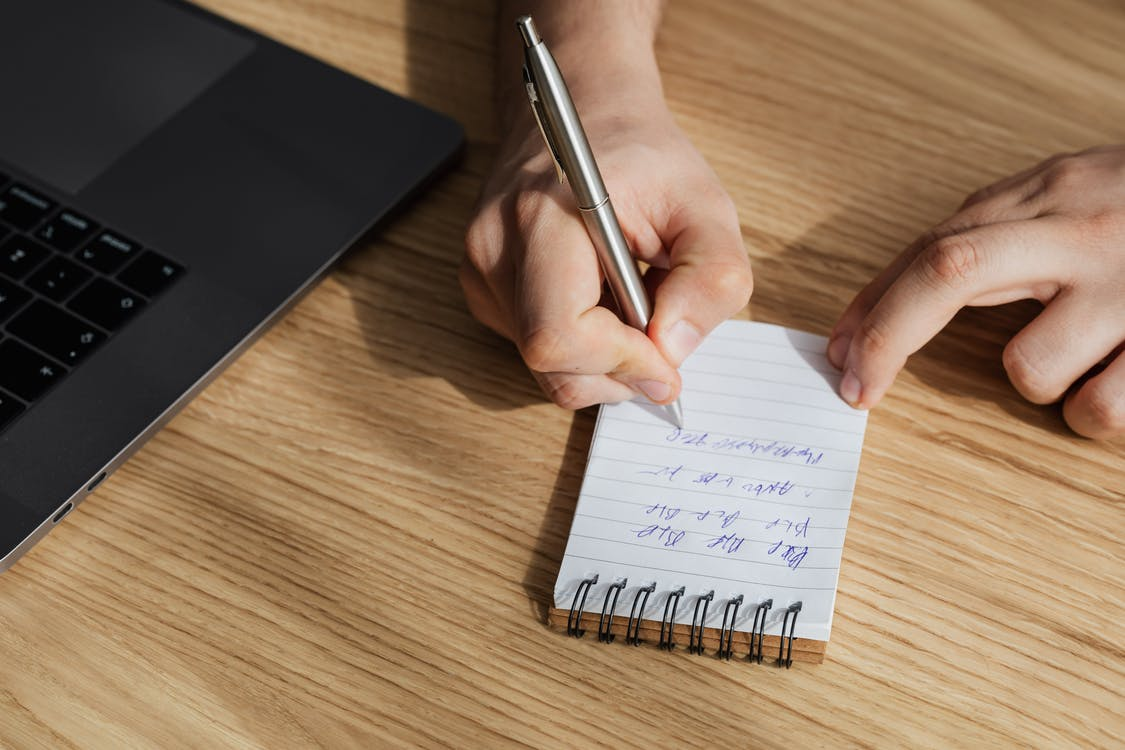 Crop anonymous employer making notes during work on laptop
