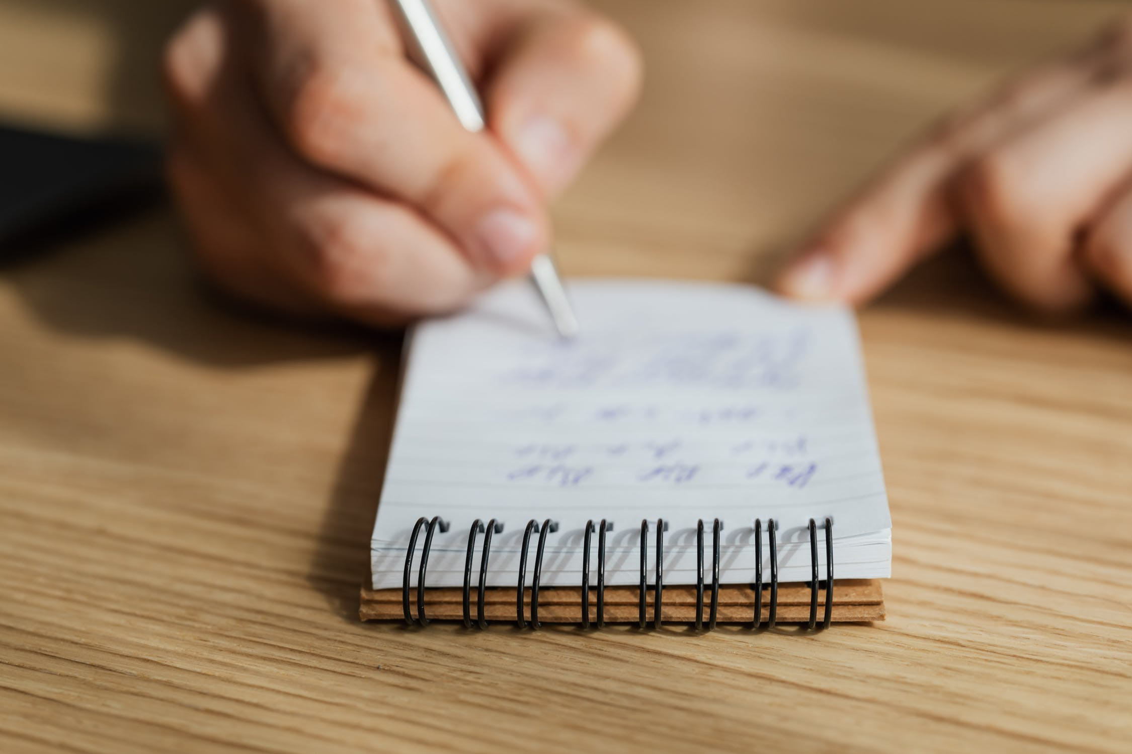 A person writing in a notepad. Photo by pexels user Karolina Grabowski. Used courtesy of pexels.com.
