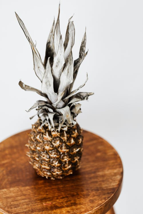 From above of ripe whole sweet pineapple on round wooden coffee table against white background