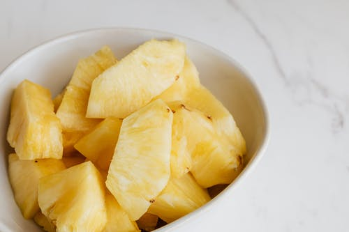 From above of fresh pieces of ripe pineapple served in white deep plate and placed on marble table