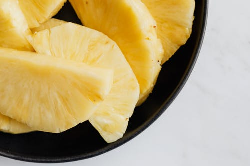 Fresh pineapple slices in black bowl