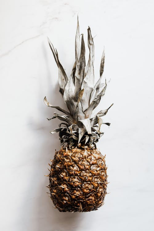 Whole pineapple on white marble surface