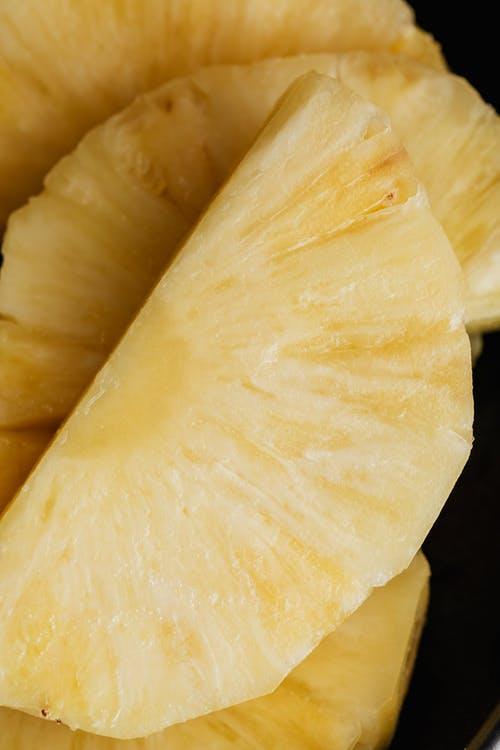 Fresh pineapple pieces on black surface