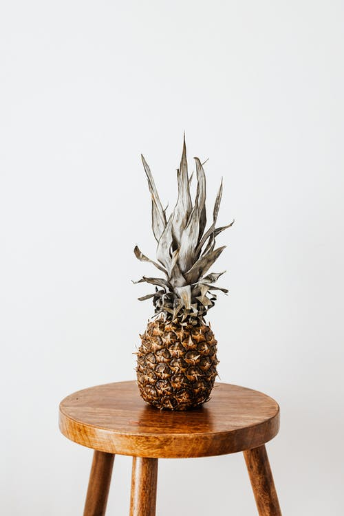 Whole pineapple fruit with dry leaves placed on small round wooden table standing near white wall