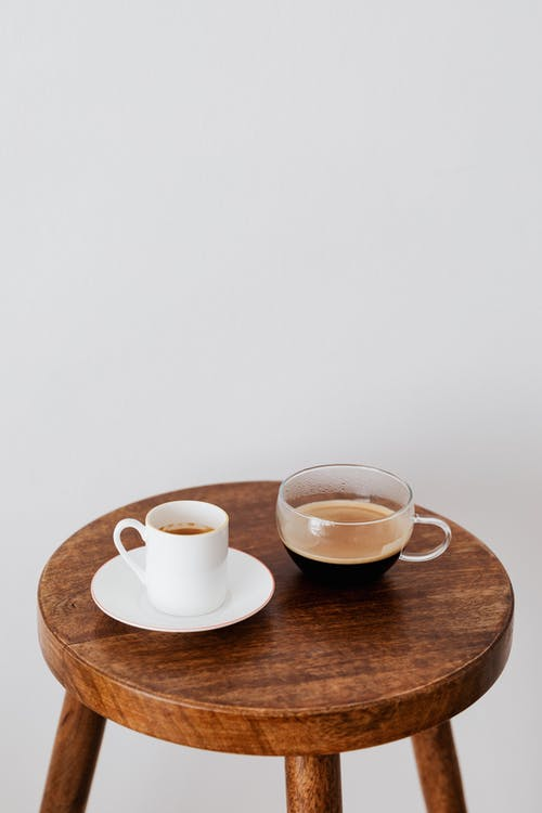 Fresh coffee in ceramic white cup and wide glass cup placed on round wooden table near white wall