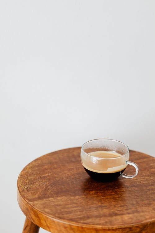 Fresh black coffee in wide cup on table