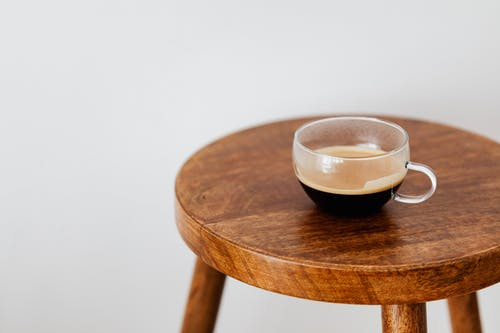 Cup of black coffee on round table
