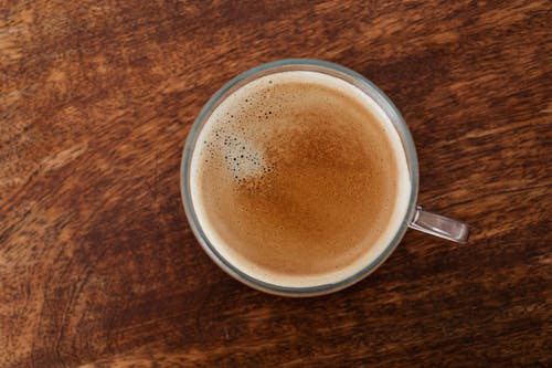 Top view of coffee with thin foam in glass cup standing on brown wooden table