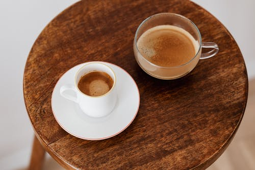 Cups of coffee placed on wooden table