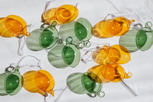 Top view of decorative yellow and green transparent glass baubles with white ribbons lying on white table and glistening in sun