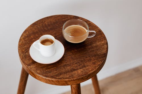 Tasty black coffee in different cups on small table