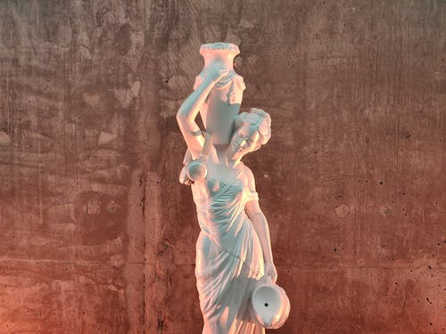 Aged masonry sculpture of female carrying decorative jug on shoulder and contemporary headphones near shabby wall