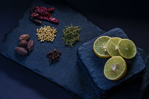 From above of dried chili peppers near thyme and pine nuts with cloves and ripe lemon slices on stone board
