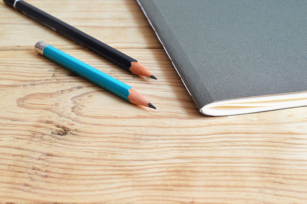 A note pad and two pencils sitting on a desk. Photo by Pexels user Skitterphoto. Used courtesy of Pexels.com.