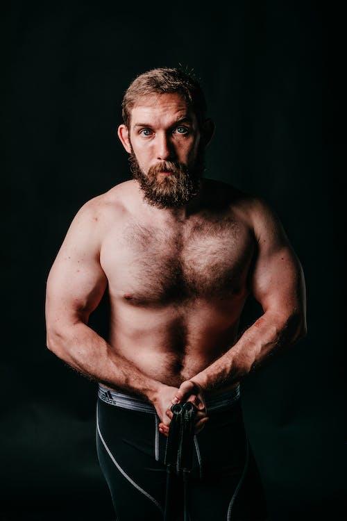 Muscular brutal sportsman with beard on black background