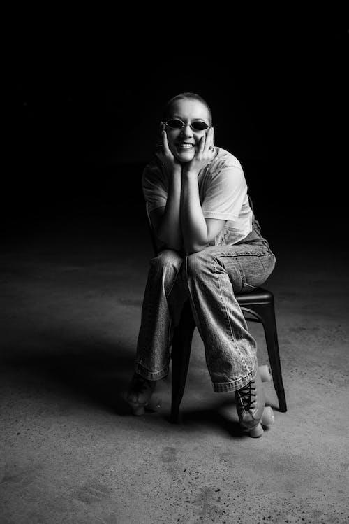 Smiling trendy woman in roller skates on stool